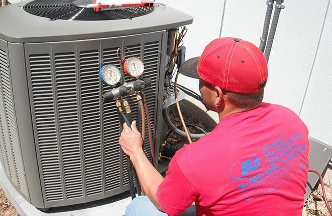 technician working on HVAC unit - A-Plus Air Conditioning & Home Solutions